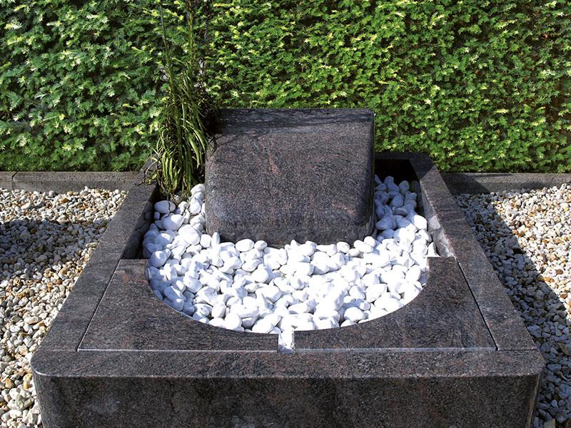 Urnengrab aus poliertem Granit mit abgerundeter Einfassung, formschönen Abdeckplatten und liegendem Grabstein in Kissenform