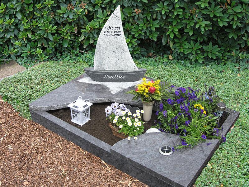 Urnengrab mit Einfassung und Abdeckplatten in Wellenform mit mehrteiligem Grabstein in Schiffform aus bicolor Granit