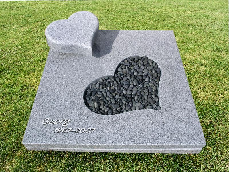 Urnengrab mit Abdeckplatte und ausgearbeitetem Herz für Kiesfläche sowie Liegestein in Herzform