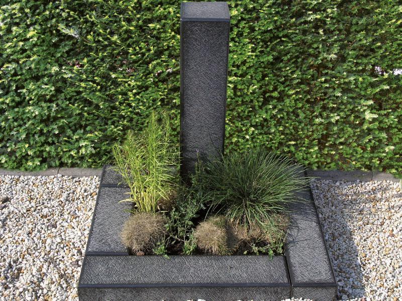 Handwerklich bearbeitetes Urnengrab aus Kalkstein mit schlichter Stele