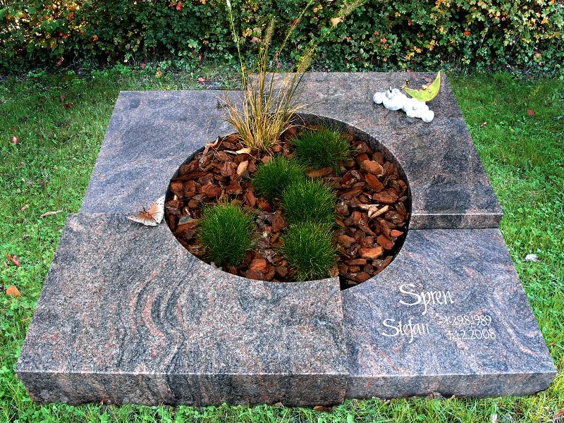 Mehrteiliges Urnengrab mit Abstufungen und kreisrundem Teilausschnitt für Bepflanzung