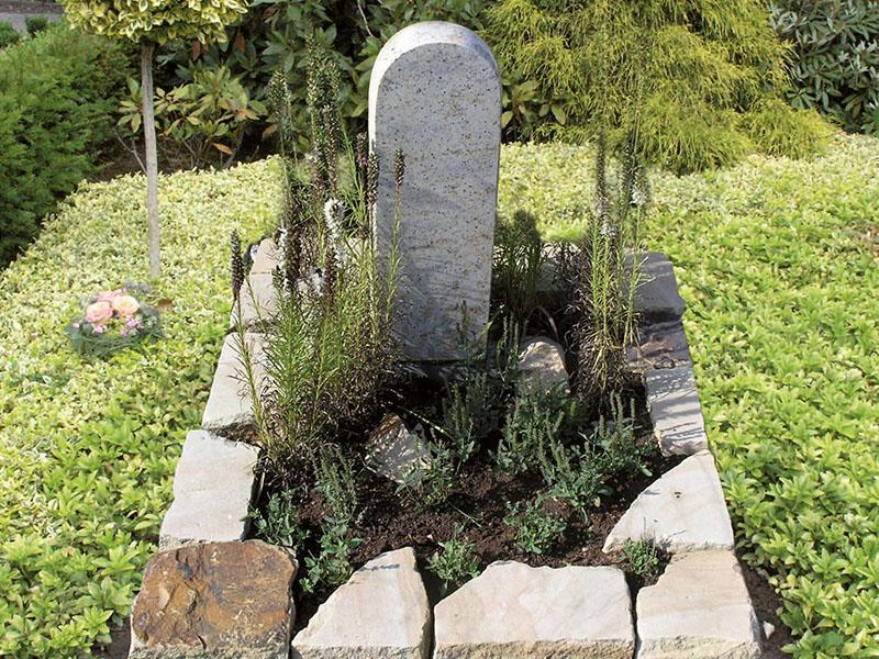 Urnengrab mit Brockeneinfassung aus Sandstein mit Stele in hellem Granit