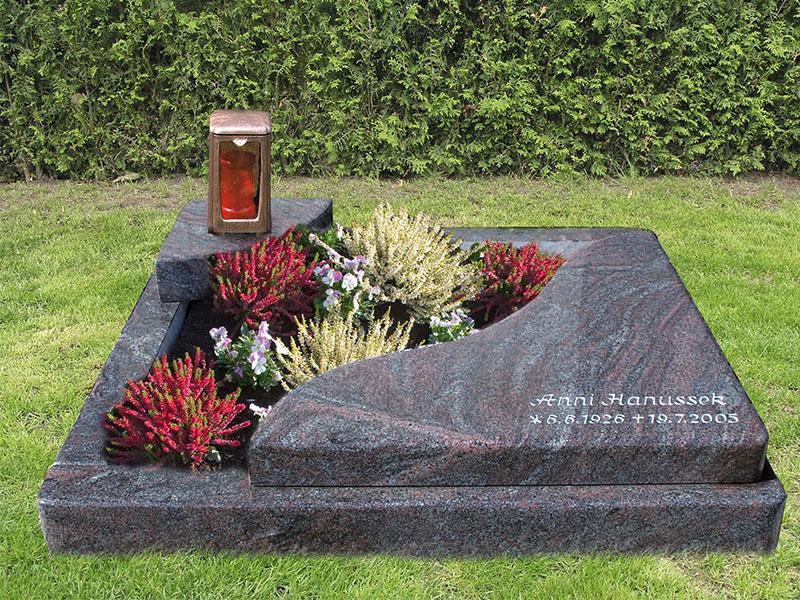 Urnengrab mit Einfassung und zwei Teilabdeckungen in Wellenform mit Bronzelampe und Inschrift