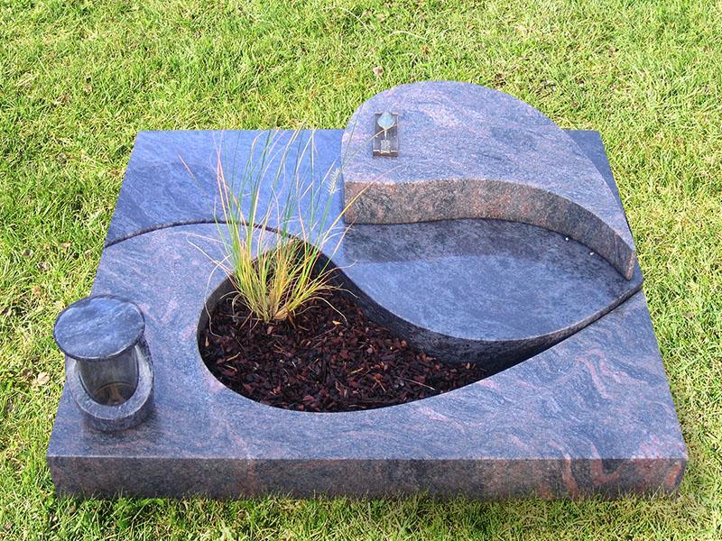 Modernes Urnengrab aus zwei Granitsorten mit formschönem Teilausschnitt und dazu passendem Liegestein sowie Grablampe aus Stein