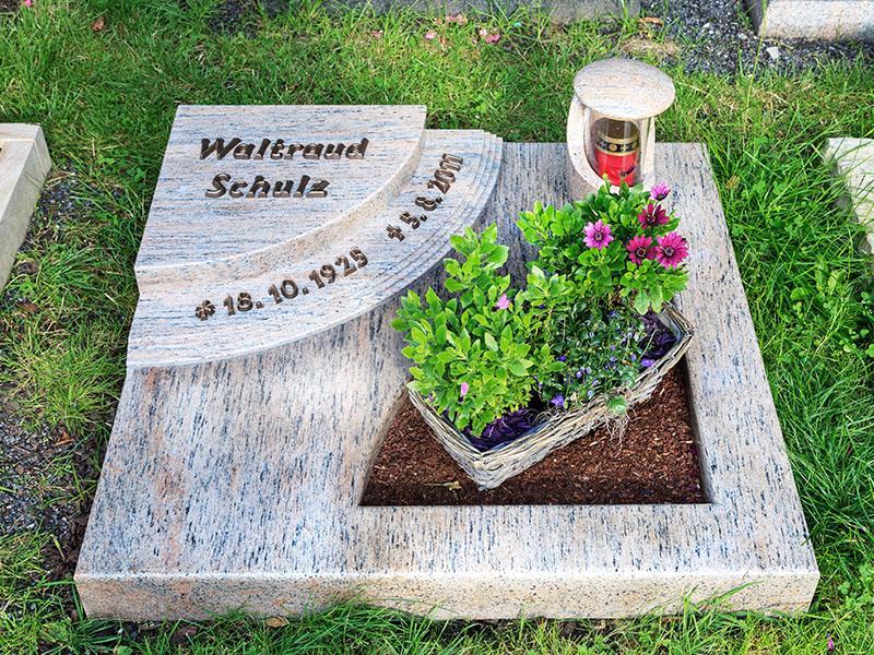 Mehrteiliges Urnengrabmal aus hellem Granit mit Bronzeschrift und passender Steinlaterne