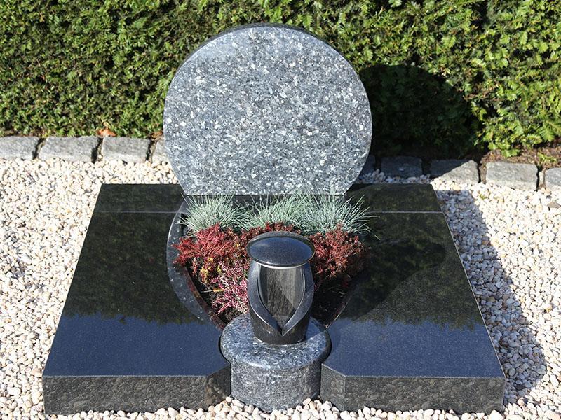 Mehrteilige Urnengrabplatte aus bicolor Granit mit integrierter Steinlampe und Grabstein in Kreisform
