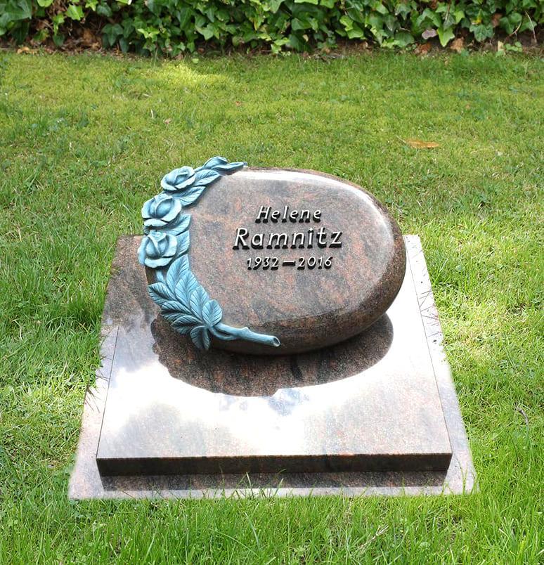 Schlichtes Urnengrab aus zwei Grabplatten mit liegendem Grabstein und handwerklich gearbeiteten Rosen